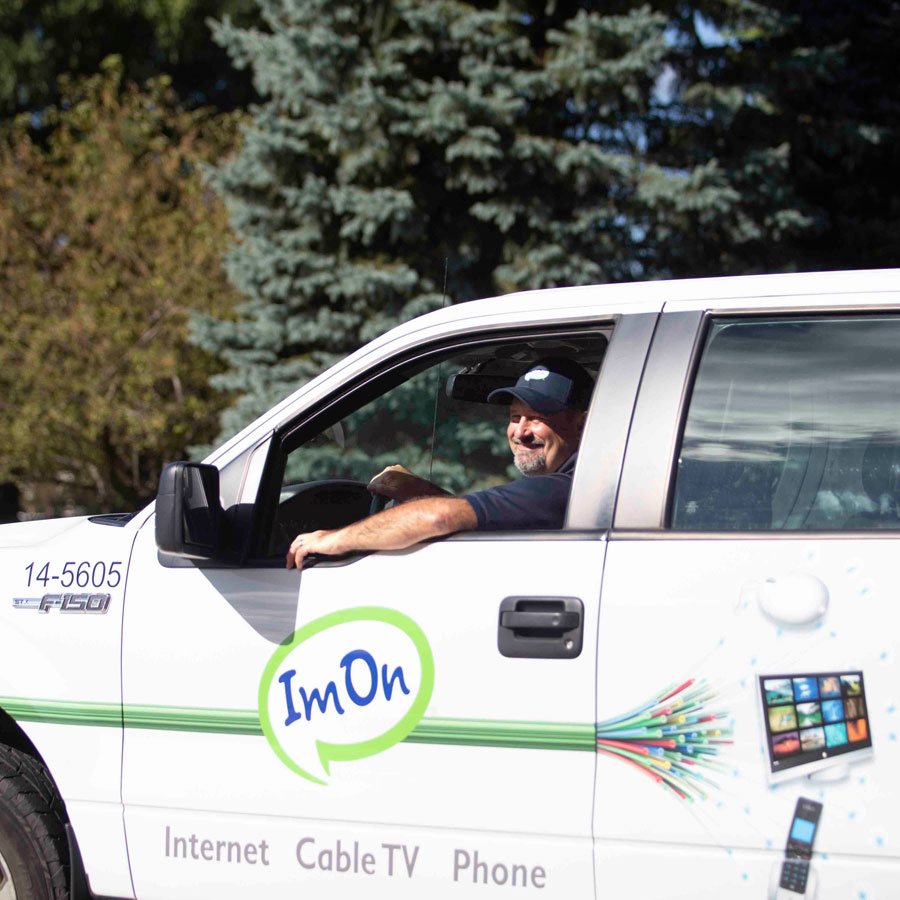 ImOn construction technician driving his ImOn truck in a new service area neighborhood.