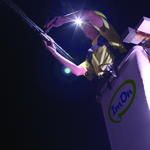ImOn technician in bucket working on network fiber hanging from a pole at night.