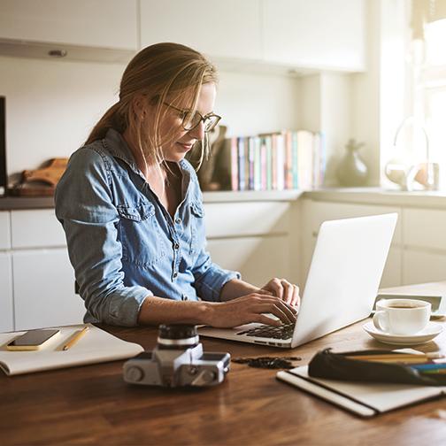 Women working on laptop on kitchen counter.