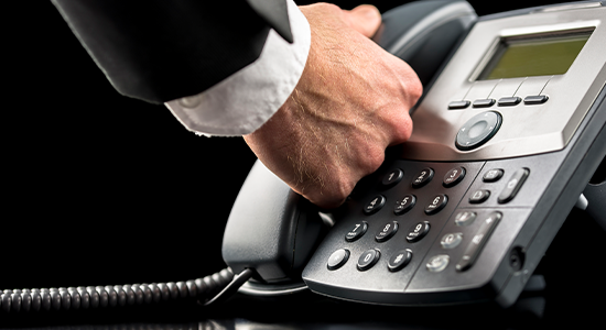 Business man reaching for receiver on office phone.