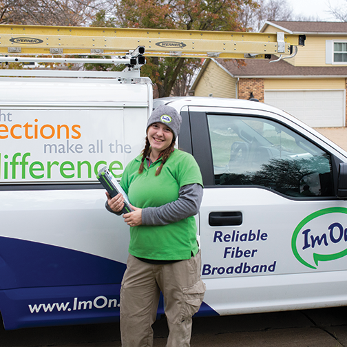 ImOn female install technician standing in front of an ImOn truck ready to start Internet install at customer's home.