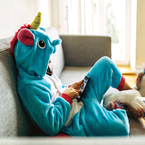A child wearing a unicorn PJs playing on his tablet.
