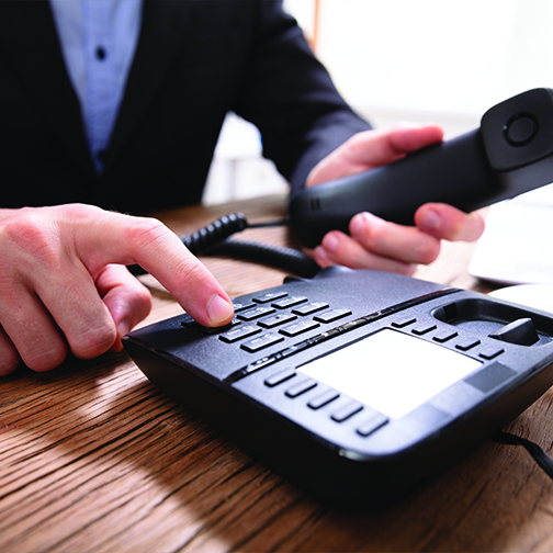 A close up shot of an business man lifting phone receiver and calling.