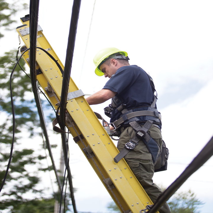 ImOn residential install technician on a ladder against a pole working on network fiber.