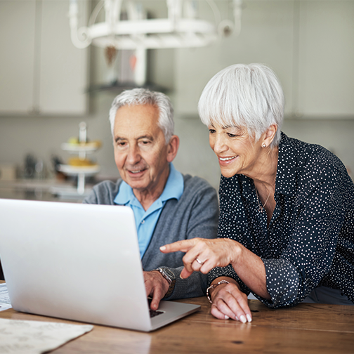 Older couple at kitchen table looking at their laptop.