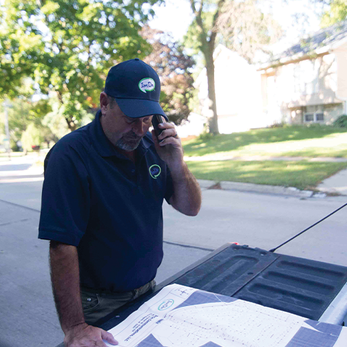 ImOn construction technician looking at a map on the tailgate of his work truck speaking on the phone in a new residential expansion neighborhood.